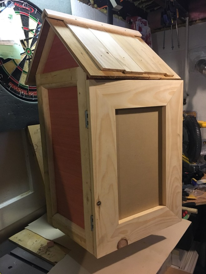 A finished little free library with red plywood panels and pine trim. Plastic window covered in protective brown film.