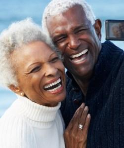 Senior Couple With Camera On Beach