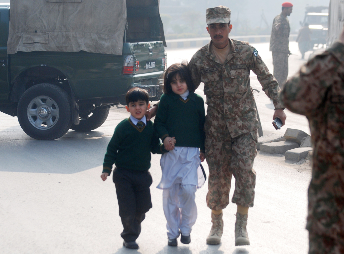 A soldier escorts students from the Army Public School in Peshawar during the attack by Taliban gunmen.