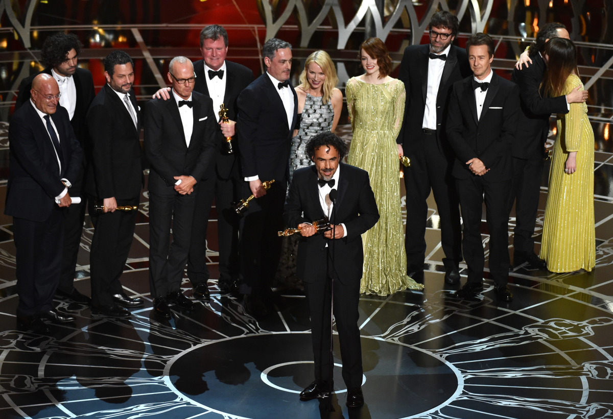 "Alejandro González Iñárritu accepts the Best Picture prize for ""Birdman,"" surrounded by the film's cast and crew."