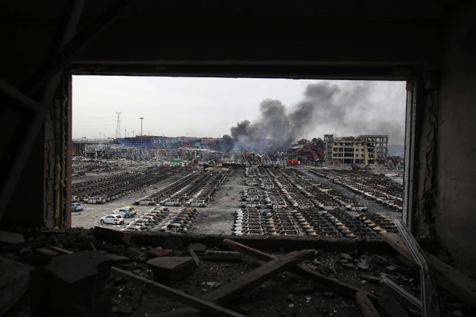 Charred shells of cars lie strewn across lots near the blast center, and the scorched skeletons of buildings that housed families and office workers remain sheathed in thick plumes of grey smoke.