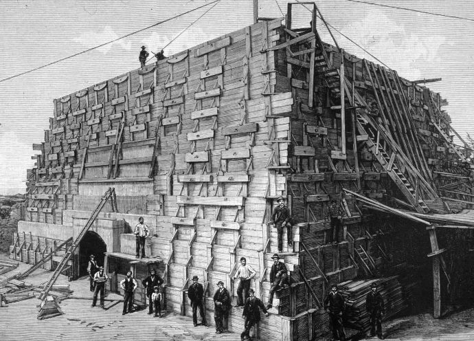 Workers pose next to the foundation they were constructing to use as the base for the Statue of Liberty, on Bedloe's Island, New York City.