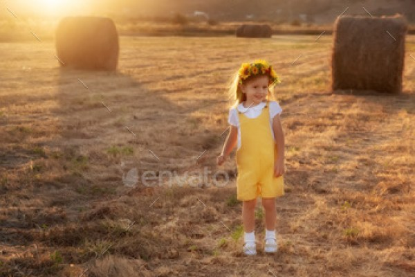Happy girl child in yellow dress runs in autumn field