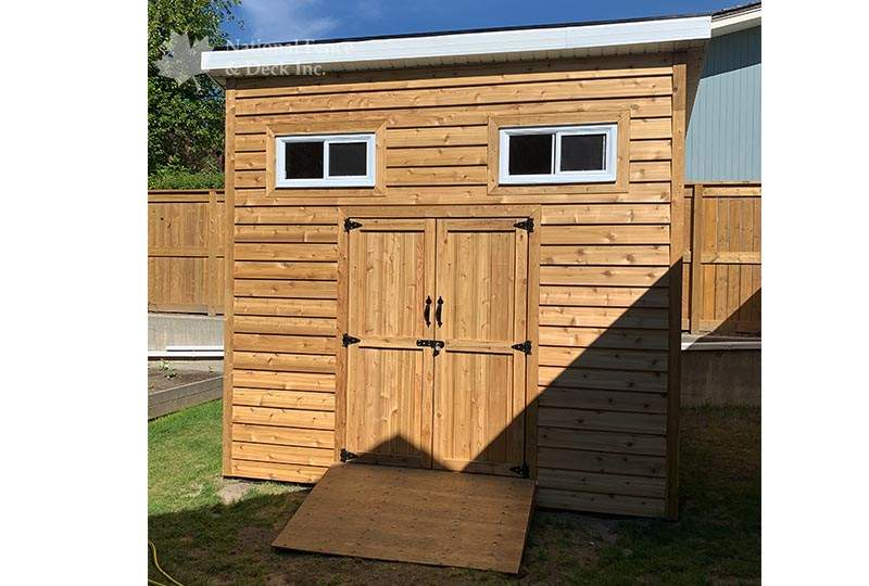 Custom built shed with cedar siding and door