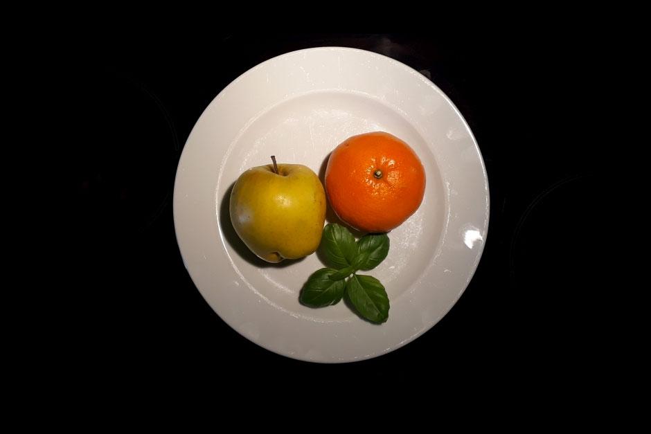 Teller mit Apfel, Orange und Basilikum