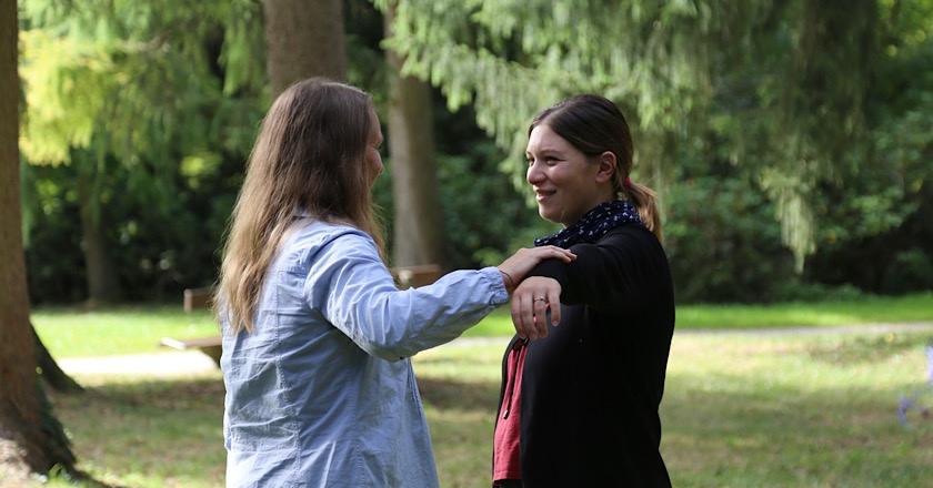 2 Frauen auf der Wiese im Wald beim Muslektesten