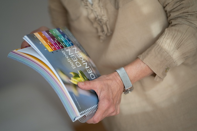 """Frauenhand mit Buch in der Hand. Buch """"Befreie dein Denken"""" und die Frau mit einer beigen Bluse und einer silbenen Uhr am Handgelenk...."""