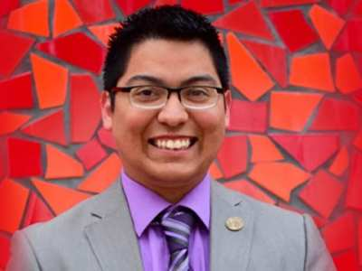 Building a Young Leader Leroy Berrones-Soto Standing by a Red Tiled Wall