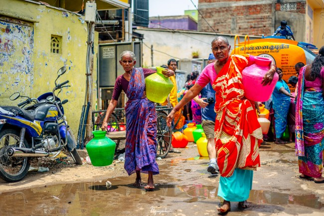 The people of a neighborhood is carrying containers of clean water home. They receive water from a delivery tanker truck that transport clean water all around the city.