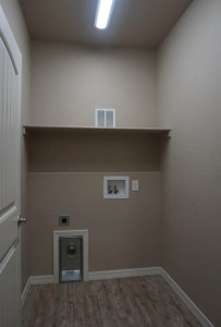 Laundry room has a self over the washer/dryer area
