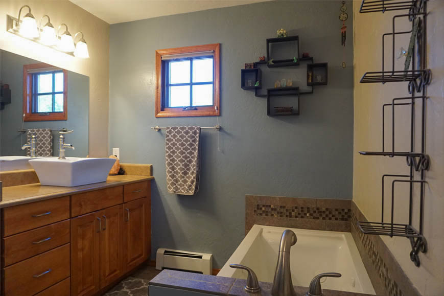 Master bath has a jetted tub, spa shower, storage vanity with vessel sink, & toilet