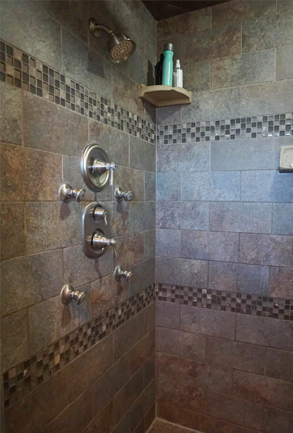 Spa shower in the master bath has a rainfall shower head, adjustable shower head, and additional nozzles.