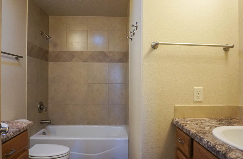 The upstairs hall bath has double vanities and an in-tub shower