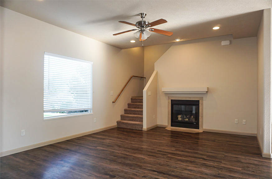 Living room includes a lighted ceiling fan, gas fireplace, and vinyl planked floors.