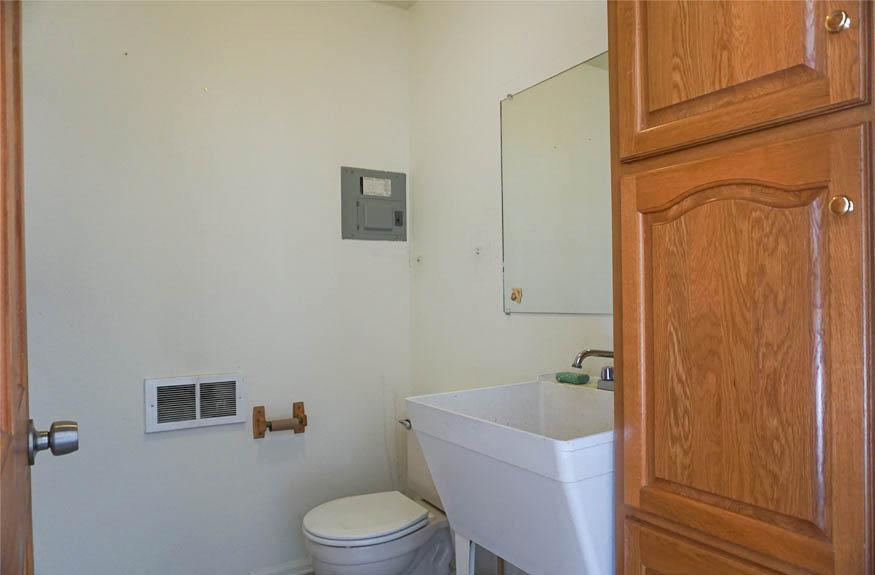 Half bath in the garage of 3078 Colorado Avenue has a deep utility sink and cabinet storage.