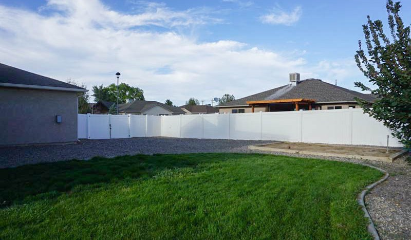 2995 Golden Hawk has a large back yard with grass, a garden area, and graveled RV parking area.