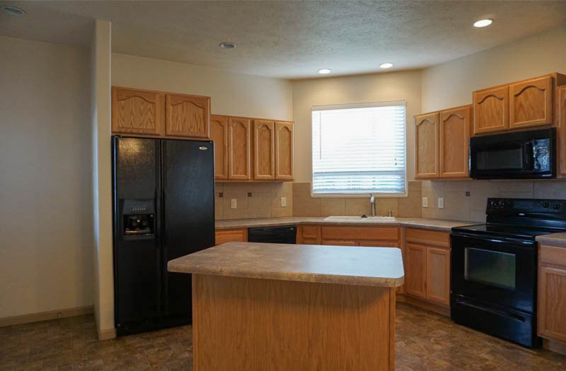 the kitchen of 2995 Golden Hawk Way includes all appliances, an island, walk-in pantry, and access to the back patio.