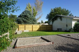 Grassed side yard of 535 Oriole has raised bed planters