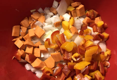 Chopped vegetables in a bowl ready for seasoning and olive oil.