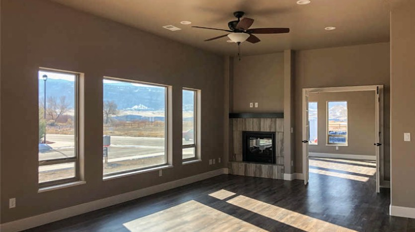 The Living room of 1305 Niblick Way has a gas fireplace, and large windows facing south towards the Colorado National Monument