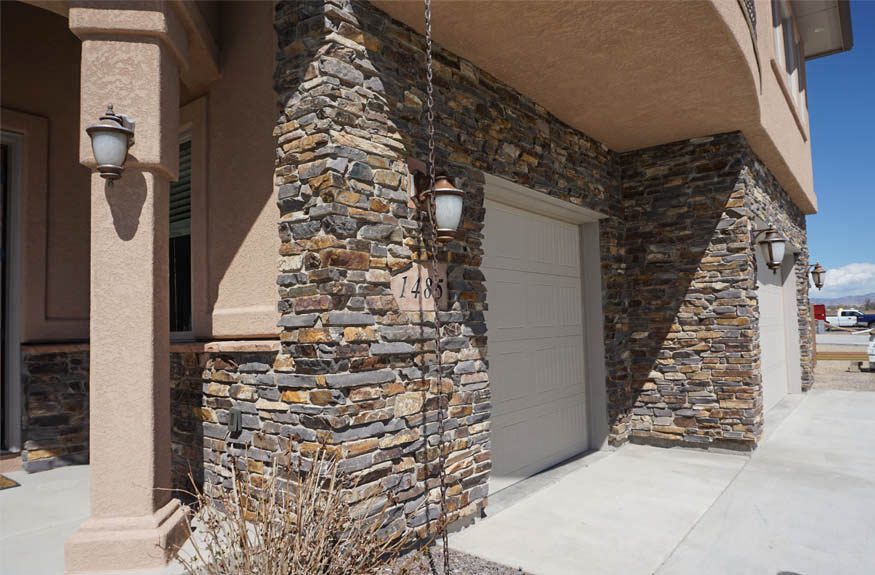 1485 Adobe Falls has natural stone laid in a ledgestone style on the exterior.