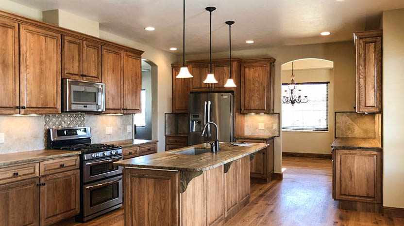 The kitchen in 1485 Adobe Falls Way has alder soft close cabinets, sandalwood natural stone countertops, recessed lighting, under cabinet lighting, and pendant lighting. The large island countertop has breakfast bar seating near a nook area.