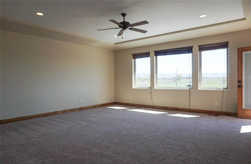 The large master bedroom in 1485 Adobe Falls Way has large, east-facing windows, recessed lighting, a ceiling fan, and a private balcony.