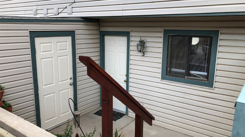 The back patio of 103 Bacon Ct #3 has an attached storage area and access to the parking area behind the unit.