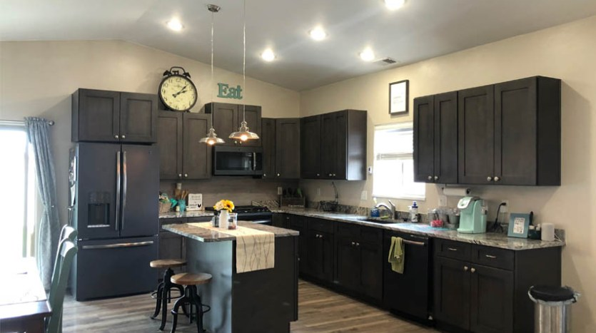 The kitchen of 2840 Kelso Mesa Dr. has shaker-style dark wood cabinets and GE black slate appliances.