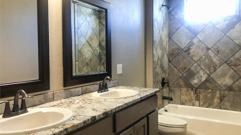 The full bath includes a double sink vanity, in-tub shower, and toilet.