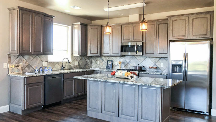The kitchen of 1484 Shoreline has soft close cabinets, drop lights over the cabinets, under cabinet lighting, and granite countertop. The GE appliances are included.