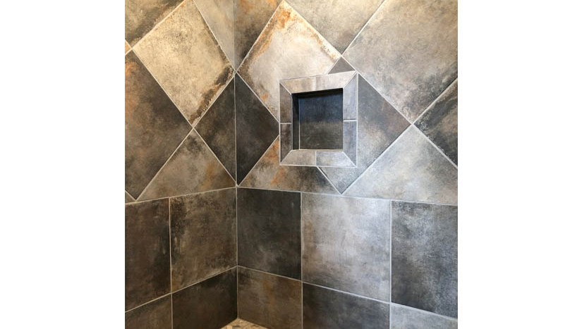 The roll-in shower in the master suite of 1446 Shoreline Dr has custom tile work, a shampoo cubby, and brushed nickel Moen faucets.