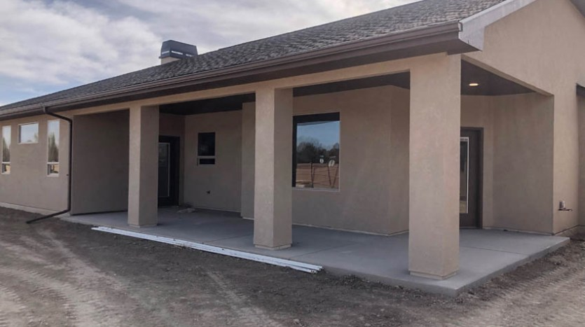 The back patio is covered, and has large pillars. It is accessible from the dining room and the master bedroom.