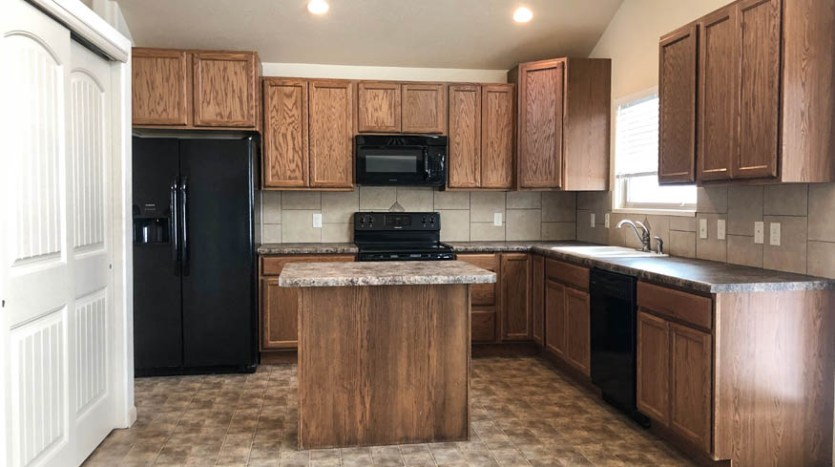 The kitchen of 165 Winter Hawk includes appliances, a center island with eating space, and a pantry. Te window overlooks the back yard.