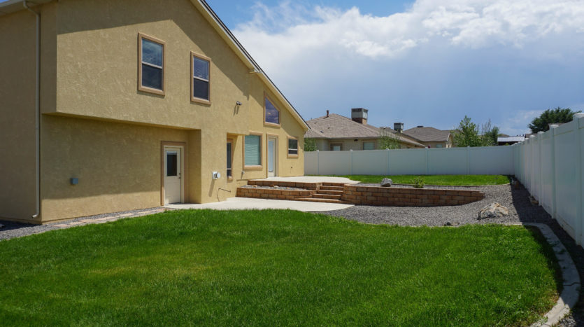 The large back yard of 165 Winter Hawk has 2 grassed areas and 2 concrete patios.