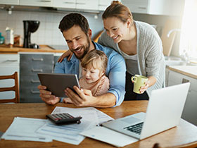 Photo of a family looking at a tablet in the kitchen