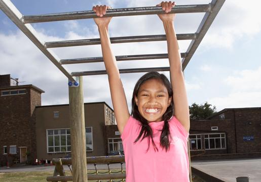 Girl hanging from monkey bars