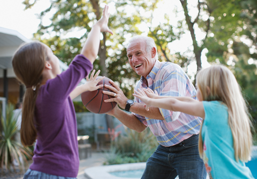 Older man playing basketball with two girls