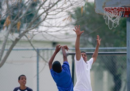Three boys play basketball