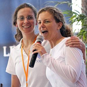 Seagram's heiresses Clare Bronfman and Sara Bronfman onstage promoting the teachings of their master, Keith Raniere. Note Clare is wearing a NXIVM shirt. Raniere has guided the sisters into commodities and real estate ventures where $100 million mysteriously disappeared. More money  - none of it evidently reported to the IRS - has disappeared since the initial $100 million which came from a trust fund.  The Bronfman's father, Edgar Bronfman Sr. died in 2013 leaving them large additional monies for Raniere's schemes.