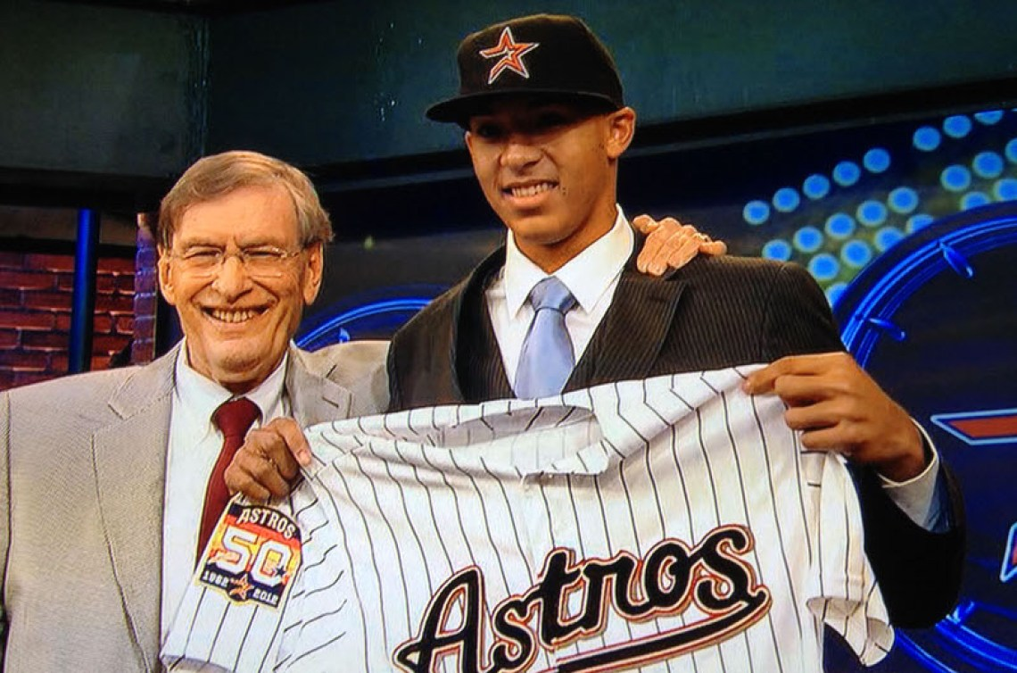 Carlos Correa holding Houston Astros jersey after being drafted