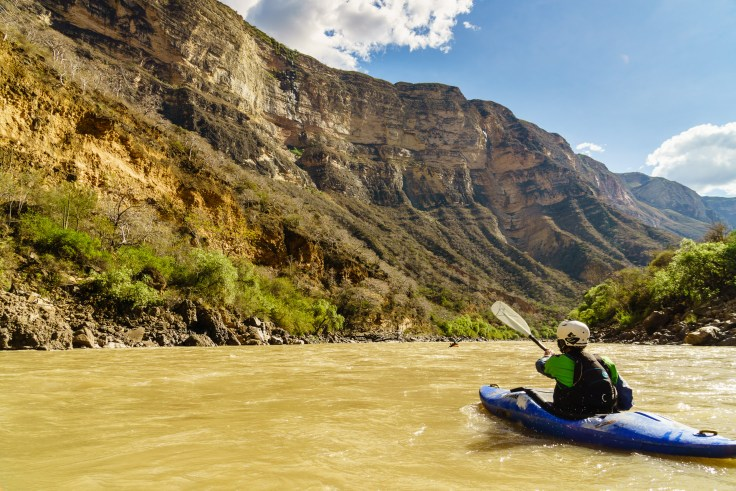 """Daphnee paddles under the canyon dubbed """"Big Wall"""" by Rocky Contos's informal guidebook."""