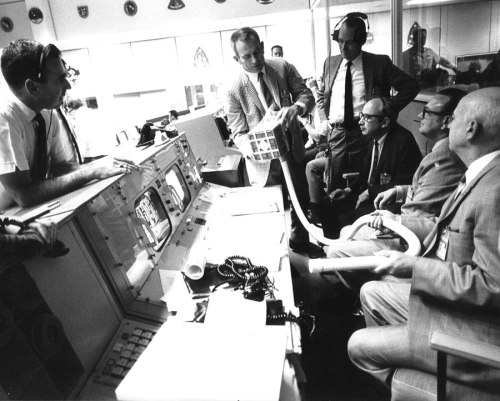 Deke Slayton (check jacket) shows the adapter devised to make use of square Command Module lithium hydroxide canisters to remove excess carbon dioxide from the Apollo 13 LM cabin