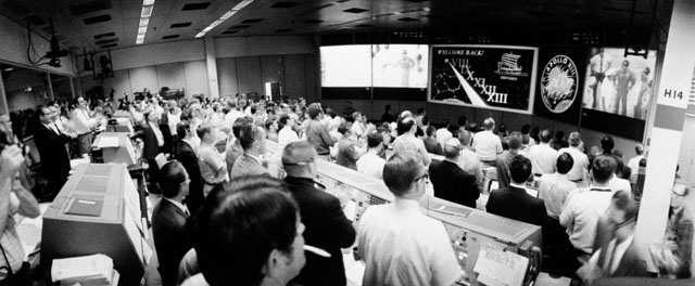 Overall view of the crowded Mission Operations Control Room during during post-recovery ceremonies for Apollo 13 aboard the USS Iwo Jima