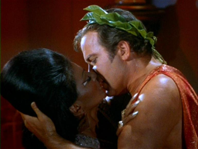 Uhura and Captain Kirk kiss. Clearly she cannot resist his manly charms. The interracial kiss on US TV.
