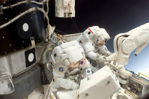 STS-114 Mission Specialists working on Discovery's cargo bay on the first EVA.