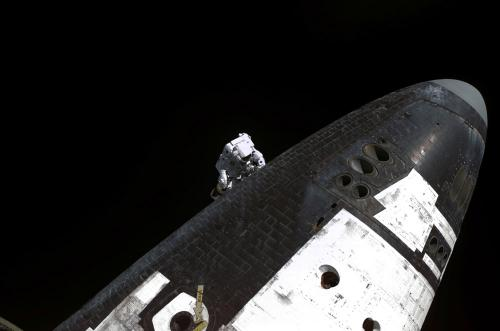 Astronaut Stephen Robinson removing gap fillers between the orbiter's heat shield tiles.