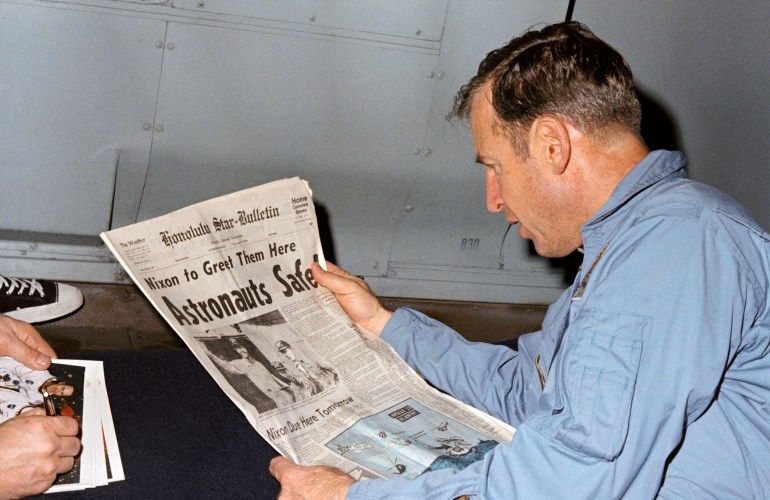 Commander Jim Lovell reads a newspaper account of the safe recovery of Apollo 13