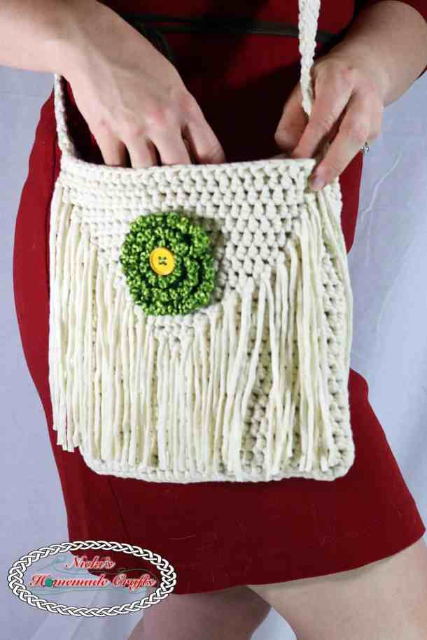 Crocheted white and green Flower Shoulder Bag worn by a women with red dress in front of a white surface