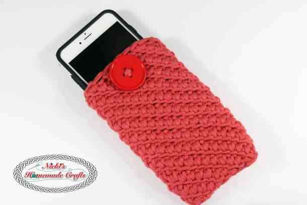 Crocheted red cellphone pouch using the Turkish star stitch displayed with an iPhone 6 plus on a white surface